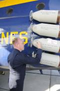 GySgt. Donny Pharr, the flight engineer who fired the JATO bottles on Fat Albert for the last time, signs the expended bottles after Bert's airshow demonstration on 14 November 2009. The bottles joined the collection at the National Museum of Naval Aviation.